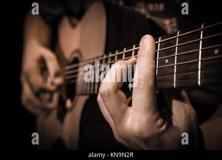 Close up of hands on the strings of a guitar, France. - Stock Photo