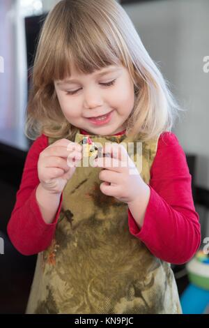 three years old little girl child blonde bang hair with red shirt green dress playing and talking to little dolls - Stock Photo