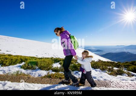 happy family winter scene of mother holding hands of three years old child hiking together in snow mountain summit - Stock Photo