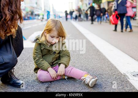 three years old blonde lovely caucasian girl child, with crying and sad expression and tear in face, next to mother, - Stock Photo