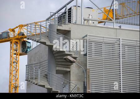 the construction crane and the building against the blue sky, France. - Stock Photo