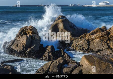 Waves smashing against rocks on the beach in Nevogilde civil parish of Porto, Portugal. Port of Leixoes Cruise Terminal - Stock Photo