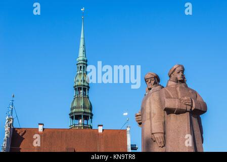 Monument of the Latvian Riflemen on the Old Town of Riga, capital city of Republic of Latvia. Saint Peter church - Stock Photo