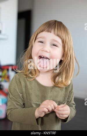 funny portrait of three years old child face, with green shirt and touching her finger, looking, laughing and sticking - Stock Photo