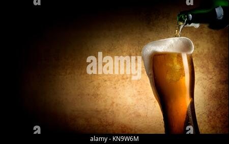 Beer pouring into glass on a textured background. - Stock Photo