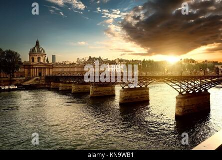 View on Pont des Arts and Institut de France in Paris at sunset. - Stock Photo