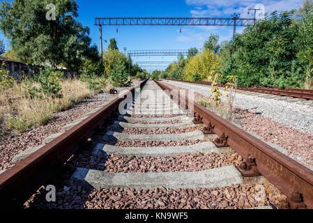 Railway tracks of abandoned Yaniv town railway station, Chernobyl Nuclear Power Plant Zone of Alienation around - Stock Photo