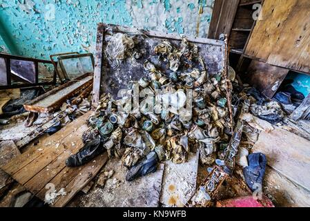 Old gas masks in abandoned Jupiter Factory in Pripyat ghost town of Chernobyl Nuclear Power Plant Zone of Alienation - Stock Photo