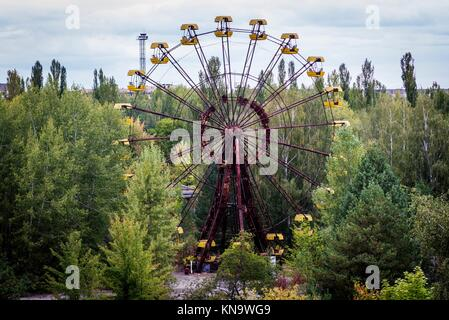 Ferris wheel in amusement park in Pripyat ghost city of Chernobyl Nuclear Power Plant Zone of Alienation around - Stock Photo
