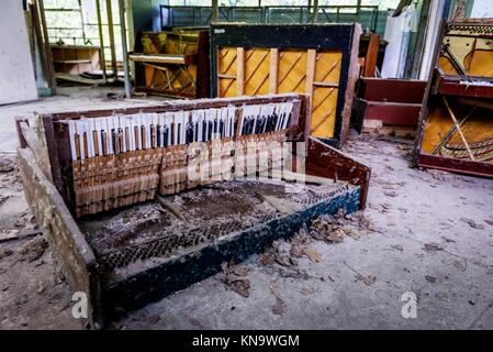 Destroyed piano in abandoned music shop in Pripyat ghost city of Chernobyl Nuclear Power Plant Zone of Alienation - Stock Photo