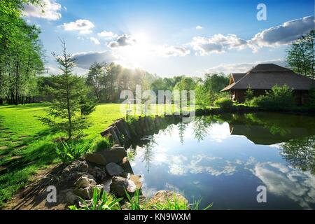 Wooden bathhouse near lake in the evening. - Stock Photo