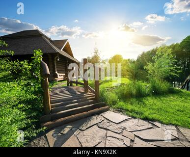 Bridge and house of log in the forest. - Stock Photo