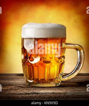 Figured mug of beer on a wooden table. - Stock Photo