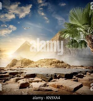 Fog around pyramids in desert at sunrise. - Stock Photo