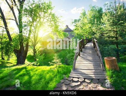 House of log and bridge in green park. - Stock Photo
