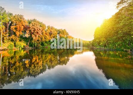 Pink sunrise over calm river in the forest. - Stock Photo