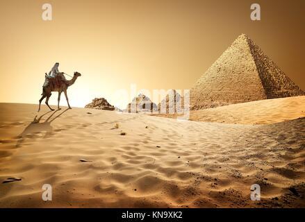 Bedouin on camel near pyramids in desert. - Stock Photo