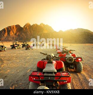 Quad bikes in desert at the sunset. Stock Photo