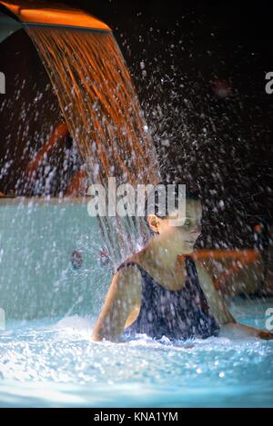 Woman relaxation in pool with waterfall. - Stock Photo