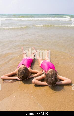 Two girls lie on your back on the sandy beach halfway in the wate. - Stock Photo