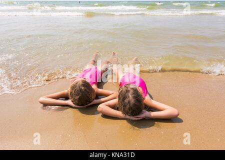 Two girls lie on your back on the sandy beach and looking at sea. - Stock Photo