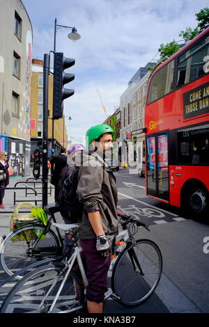 Cyclists waiting to cross road as red london bus passes by in London, England, UK - Stock Photo
