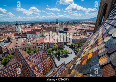 Aerial view from Saint Mary Lutheran Cathedral in Sibiu city in Romania with Council Tower and Holy Trinity Roman - Stock Photo