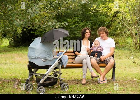 Happy mother and father with baby in park, France. - Stock Photo
