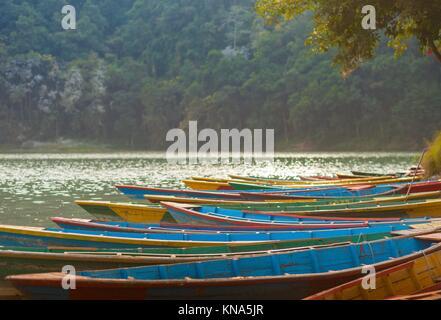 Rowboats lined up at Fewa Lake (Phewa Tal), Pokhara, Nepal with Machhapuchre in the background. - Stock Photo