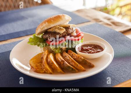 A Bleu (Blue) cheese hamburger with fries and barbecue sauce on a cafe table. - Stock Photo