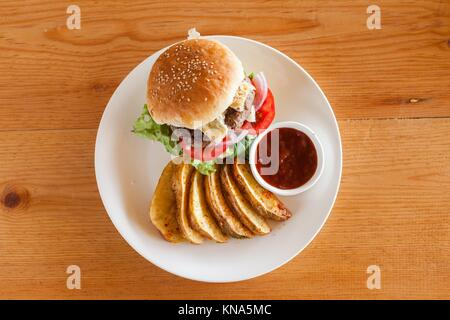 A Bleu (Blue) cheese hamburger with fries and barbecue sauce from above on a wood tabletop. - Stock Photo