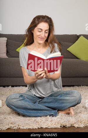 smiling happy brunette woman with grey shirt and blue jeans trousers, reading red book sitting on carpet indoor - Stock Photo