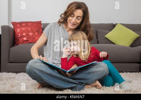 blonde child three years old, with red and green clothes, leaning on mother woman in jeans, reading together a story - Stock Photo