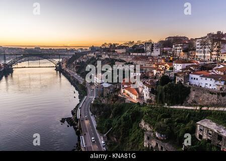 Sunset view with Dom Luis I Bridge connected cities of Porto and Vila Nova de Gaia in Portugal. Ribeira Negra Street - Stock Photo