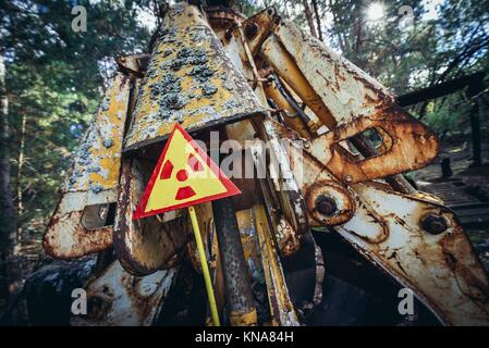 Warning sign in front of irradiated scrap bucket in Pripyat city of Chernobyl Nuclear Power Plant Zone of Alienation - Stock Photo
