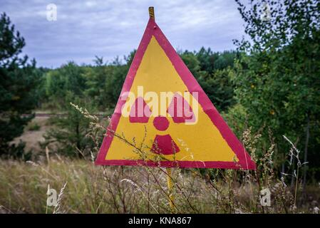 Warning sign in so called Red Forest area surrounding Chernobyl Nuclear Power Plant, Zone of Alienation, Ukraine. - Stock Photo