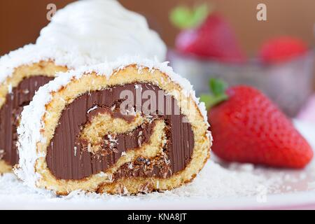 Slice of chocolate coconut cake roll decorated with whipped cream and strawberries, closeup view. - Stock Photo