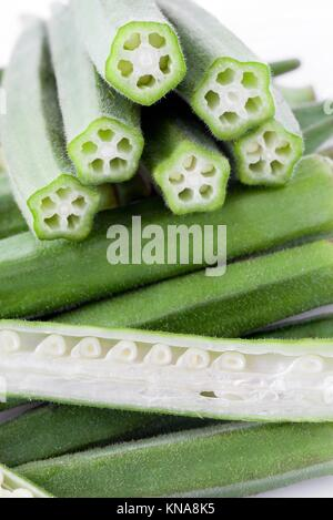 Okra pods with cut stem, whole and sectioned, vertical layout. - Stock Photo
