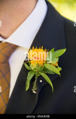 Groom wearing formal attire including this suit jacket on his wedding day in Oregon. - Stock Photo