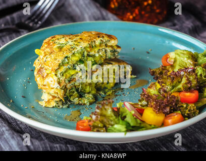 Zucchini Pancakes With salad at blue plate - Stock Photo