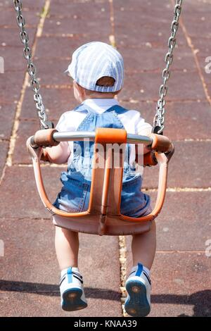 2 year-old boy playing on adapted swing. Playground toy. - Stock Photo