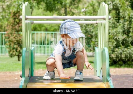 2 year-old boy playing on slider at playground. He is on the top. Balance concept. - Stock Photo