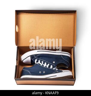 Dark blue sports shoes inside cardboard box isolated on white background. - Stock Photo