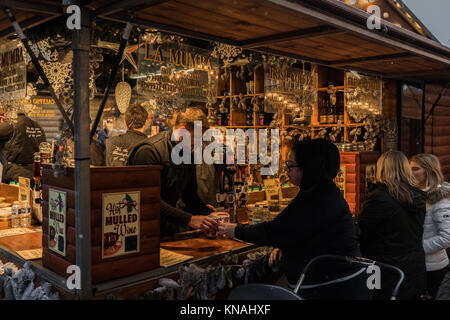 Market stall traders serve food and drink to customers at Manchester Christmas Markets Around The City, Manchester, - Stock Photo