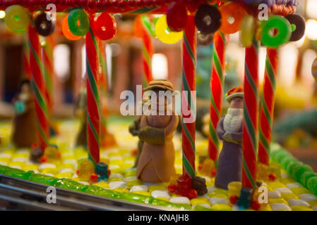 Christmas scenery with human figurines dressing up the traditional vintage winter clothes standing on the sidewalk - Stock Photo