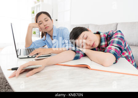 beautiful elegant female college classmate using computer doing homework together at home and studying feeling tired - Stock Photo