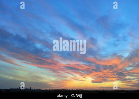 Dramatic sunset over city in spring time. - Stock Photo
