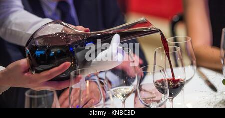 Sommelier pouring wine into glass from mixing bowl at luxury diner. Stock Photo