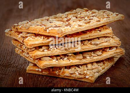 Stack of cereal cookies with seeds on a wooden table. - Stock Photo