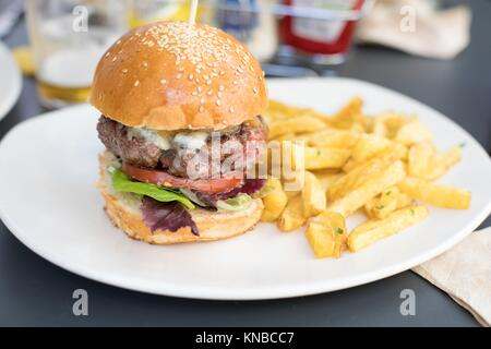 still life of beef burger, with cheese, onion, pickle, lettuce and tomato slice, inside bun bread and potatoes french - Stock Photo